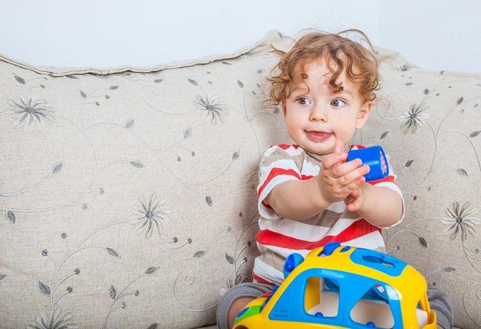 Bebê de 11 meses brincando com um carro de brinquedo