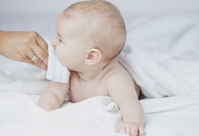 Uma mãe limpando a boca do bebê.