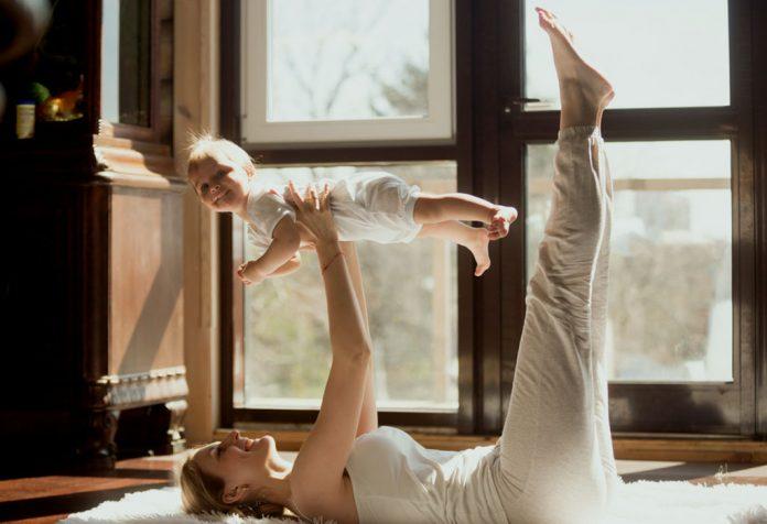 Mãe exercitando com seu bebê
