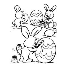 Desenho de coelhos pintando ovos de páscoa no jardim para colorir