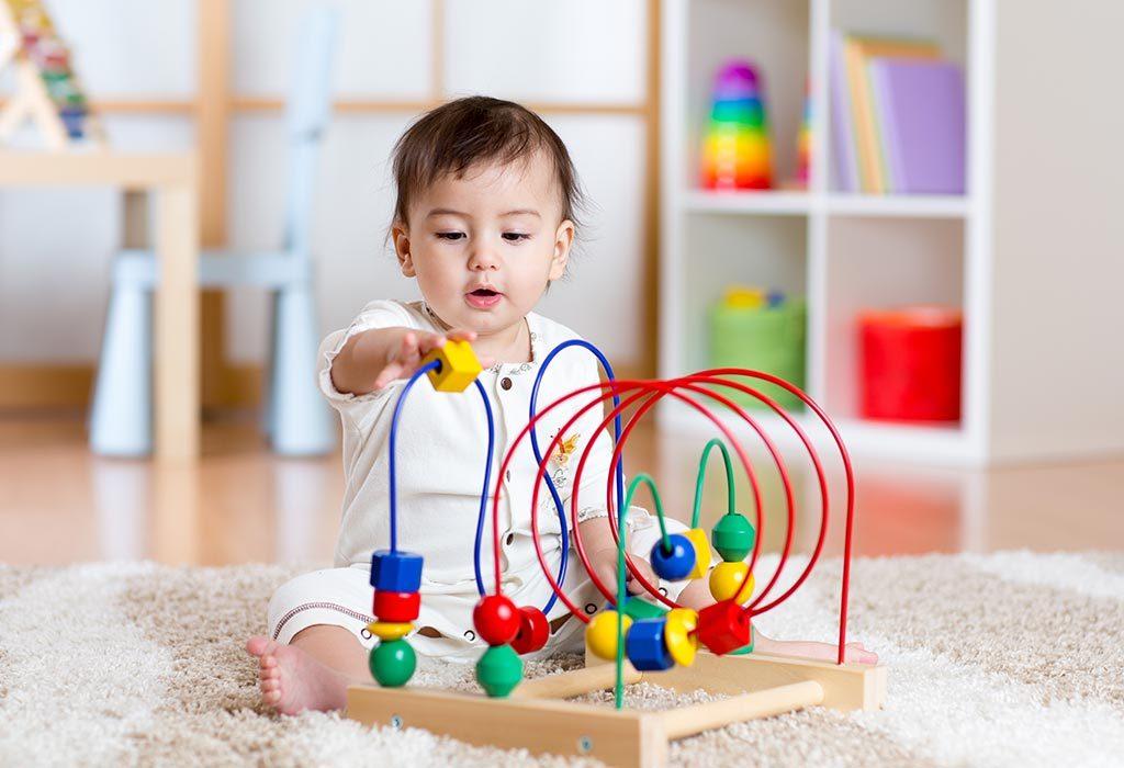 """Um bebê brincando com brinquedos """"width ="""" 1024 """"height ="""" 700"""