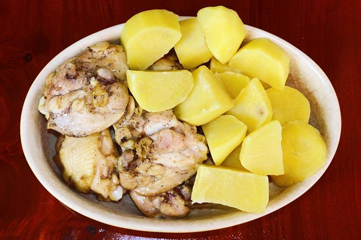 Batatas cozidas com frango frito com cebola.