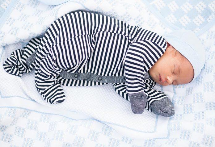 Um bebê dormindo de um lado