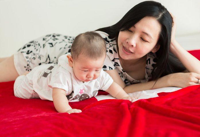 Uma mãe olhando para o bebê tentando engatinhar