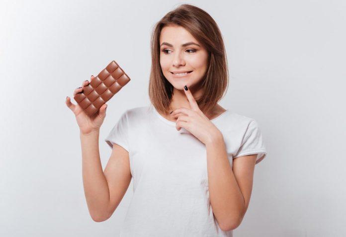 Uma mulher pensando em comer chocolate