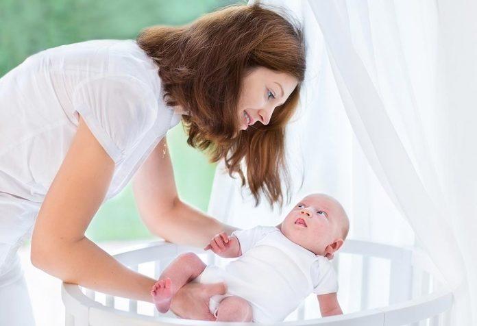 Mãe colocando bebê no berço