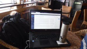 computador de viagem e lata de café