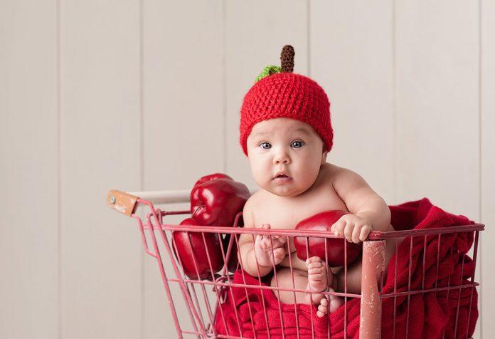 Um bebê com um chapéu de maçã