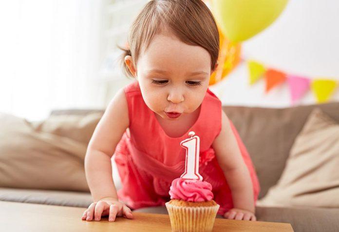 Uma menina de um ano soprando sua vela de aniversário
