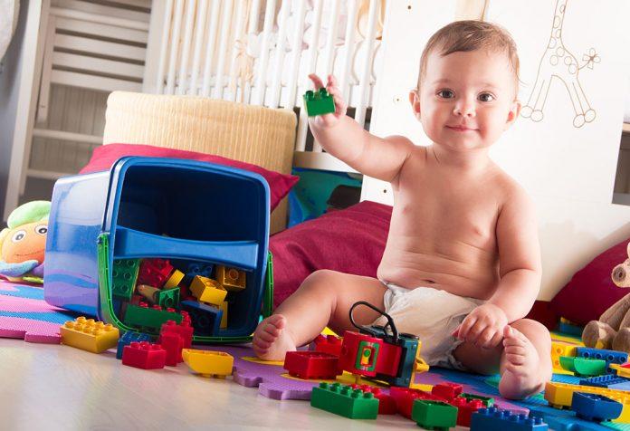 Um bebê cercado por brinquedos